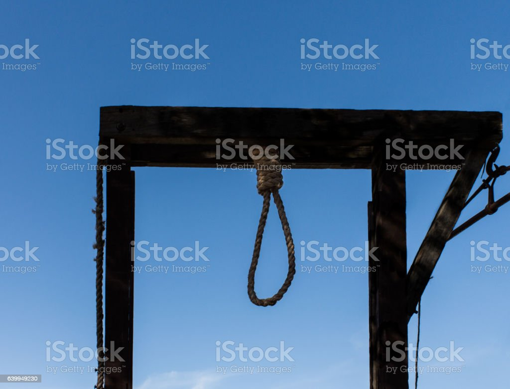 Hangman gallows with noose against blue sky stock photo