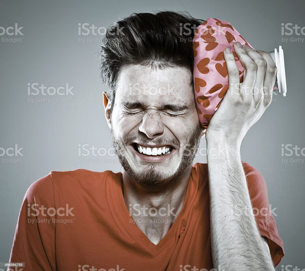 Hangover Portrait of young man  suffering from headache, cooling his head with a ice pack. Studio shot, grey background. 20-29 Years Stock Photo
