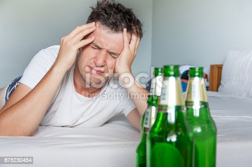 istock Hangover suffering man close up portrait with bottles of beer. 875230454