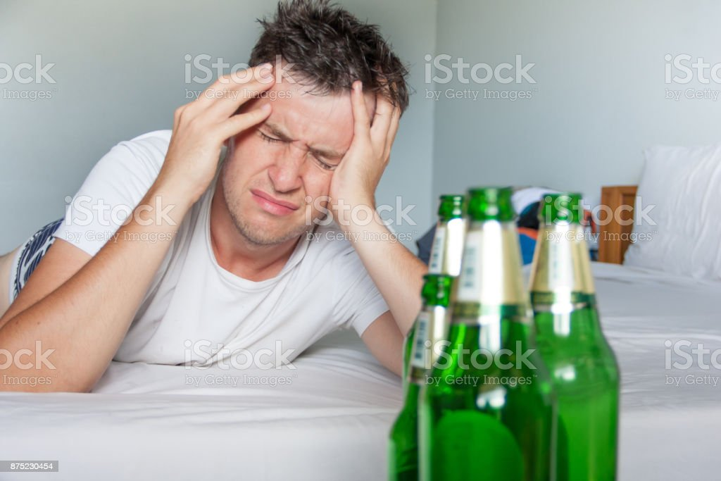 Hangover suffering man close up portrait with bottles of beer. stock photo