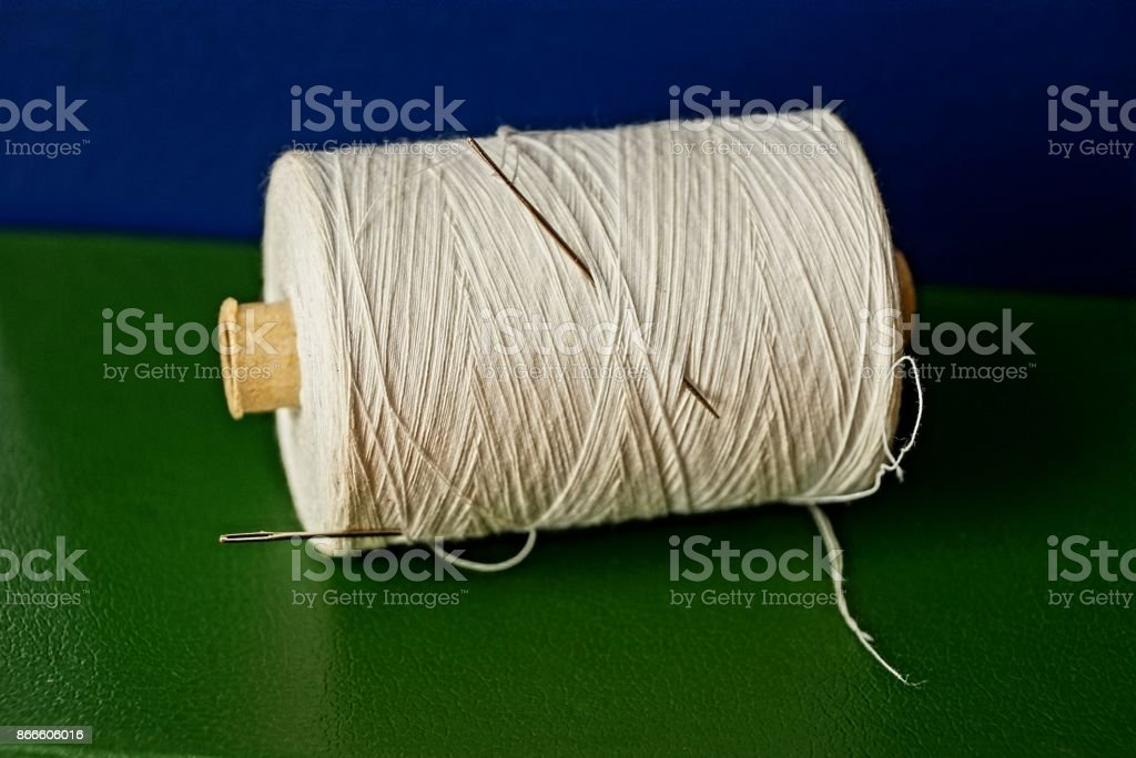 A hank of white threads and a needle on a table stock photo
