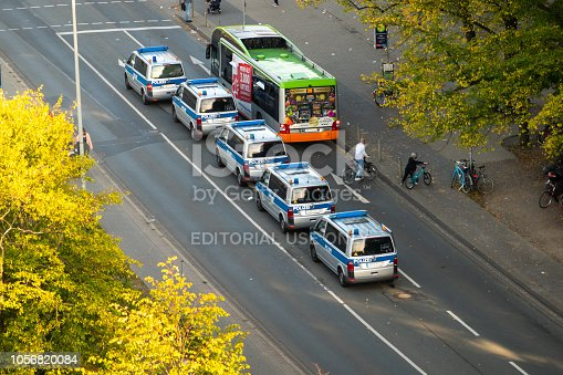 1095367134 istock photo Hannover, Lower Saxony, Germany, October 13., 2018: VW buses of the German police next to a bus of the local transport companies on the street, aerial photograph. 1056820084