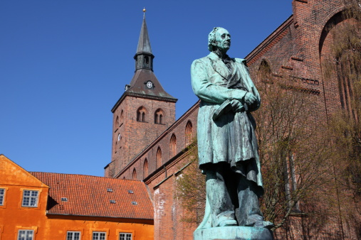 Sculpture of World Famous Danish fairy tale writer and poet Hans Christian Andersen (1805 - 1870) in front of the Sankt Knuds kirke (church) in Odense, the town where he was born.