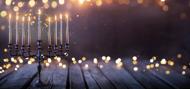 Hanukkah Abstract Defocused Background - Menorah With Bright Dust On Wooden Table stock photo
