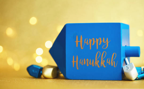 Hanukkah background with dreidel on gold and Happy Hanukkah message stock photo