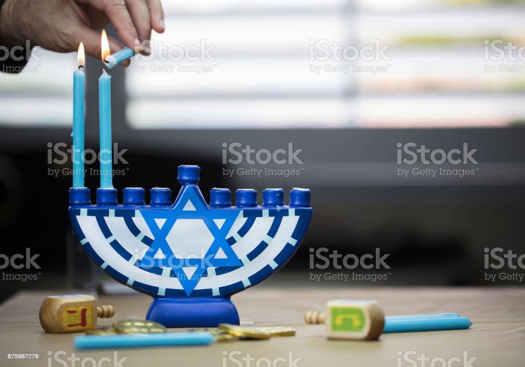 Hanukkah candles lit for the holiday celebration surrounded by dreidels and chocolate coins stock photo