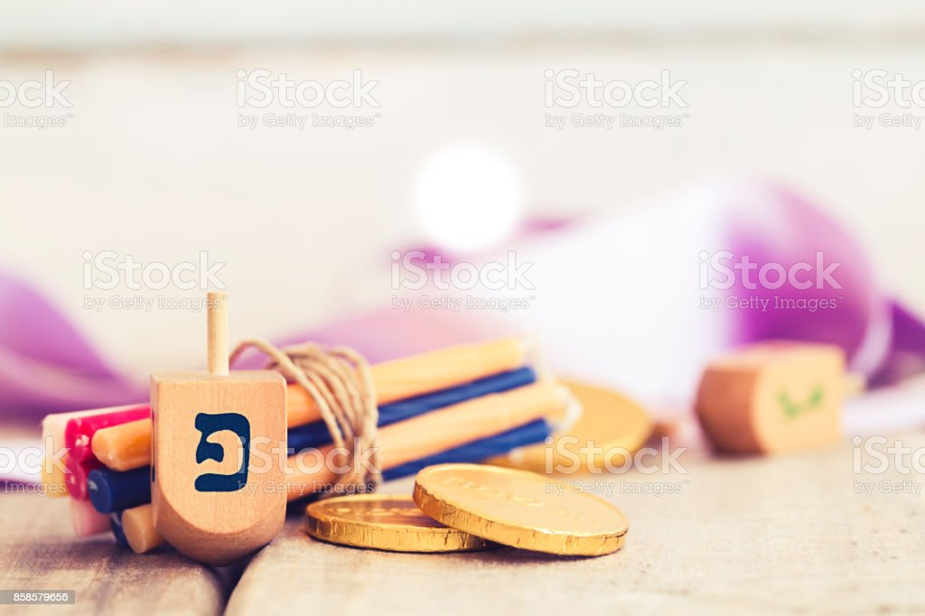 Hanukkah dreidels with some Hanukkah candles and Hanukkah coins on a vintage wood background with copy space. stock photo