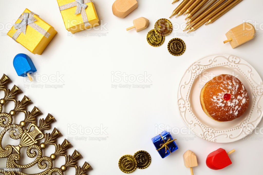 Hanukkah holiday background with menorah and sufganiyot on white background with copy space. View from above stock photo