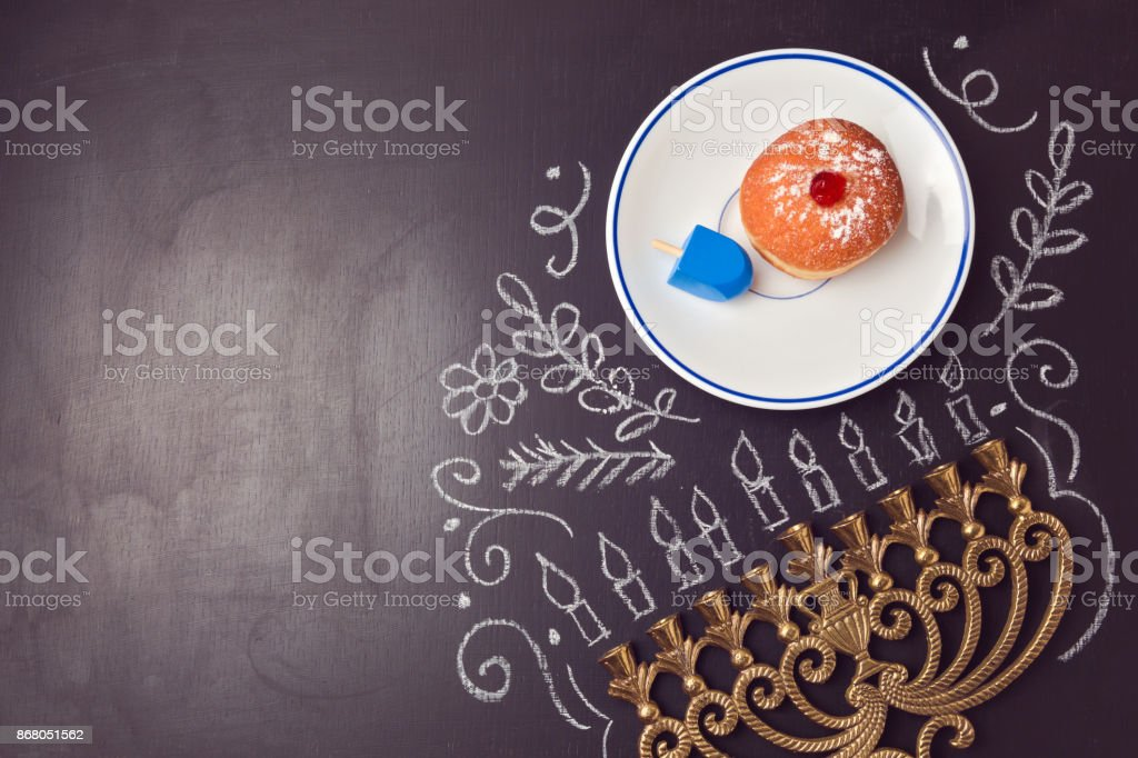 Hanukkah holiday background with menorah and sufganiyot over chalkboard. View from above stock photo