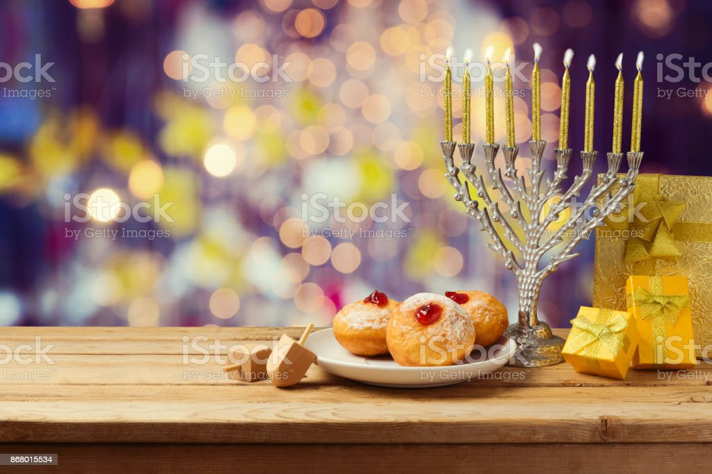 Hanukkah holiday sufganiyot and menorah on wooden table over night bokeh background stock photo