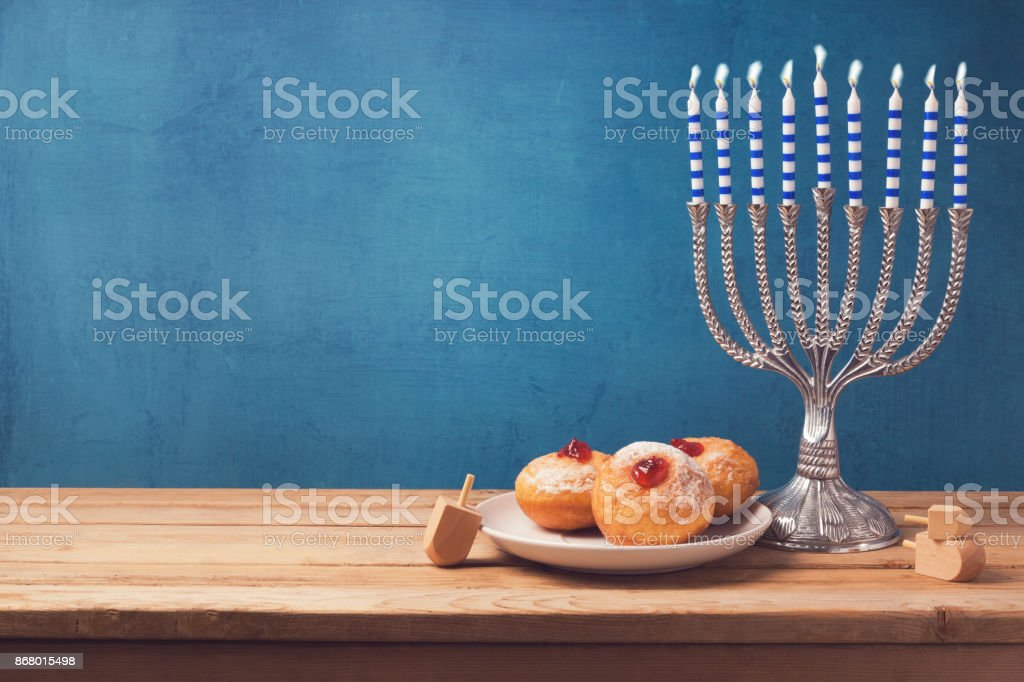 Hanukkah holiday sufganiyot and menorah on wooden table over vintage background stock photo