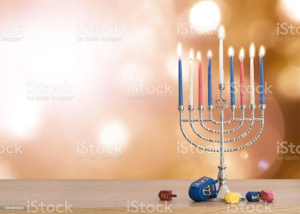 ハヌカ本枝の燭台 (ユダヤ教の燭台) 燃焼ろうそくや伝統的な Dreidrel ゲームおもちゃは木製のテーブルと秋ボケ太陽フレアとユダヤ教の祝日の背景 ストックフォト