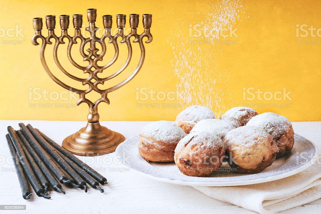 Hanukkah menorah and sufganiot on the table horizontal stock photo