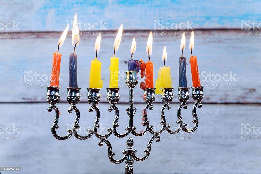 Hanukkah menorah with candles and silver dreidel. stock photo