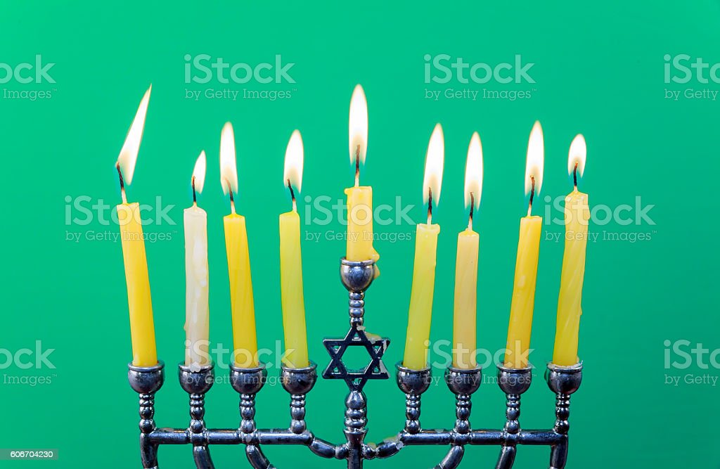 Hanukkah menorah with candles green background isolation stock photo