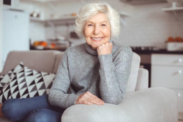 Hapiness elderly people concept. Portrait handsome grandmother in gray sweater. stock photo