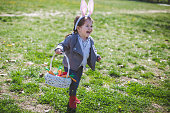 Cute toddler girl wearing a bunny ears at the park during Easter celebration, and hunting for Easter eggs.