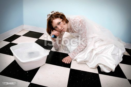 New wife scrubbing black and white tiled floor.See similar photos: