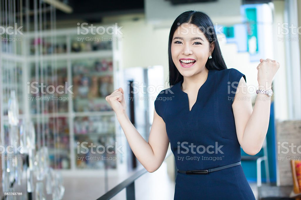 Happily excited Asian woman raise her arms - success concept stock photo