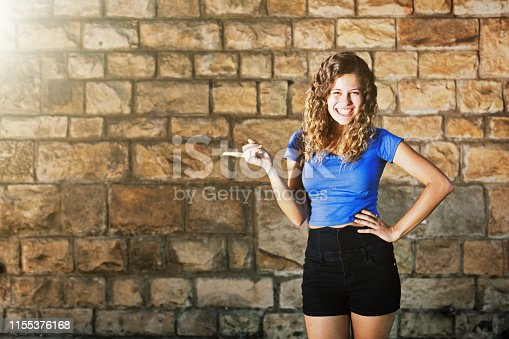 A beautiful young brunette with long curly hair stands outdoors by a sunlit brick wall, one hand on her hip, the other pointing to a blank space on the wall, smiling happily.