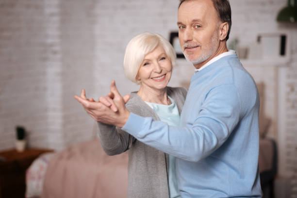 Happily smiling and dancing senior couple stock photo