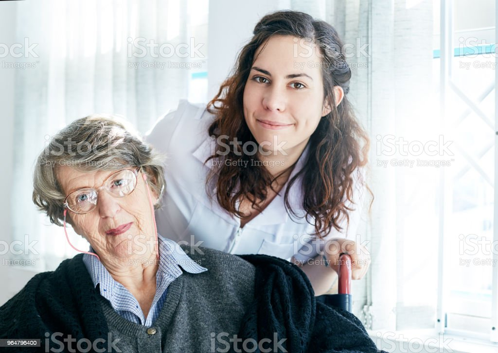Happily smiling old lady with her friendly attendant royalty-free stock photo