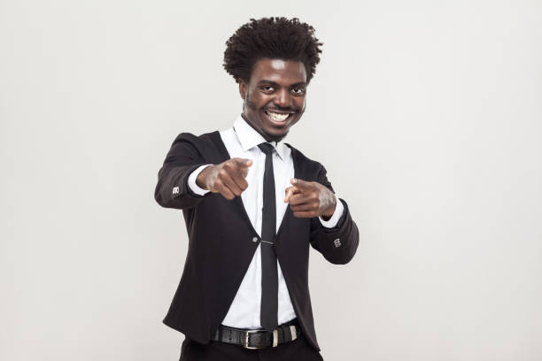 Happiness african man pointing fingers at camera. Happiness african man pointing fingers at camera. Studio shot, gray background anchor athlete stock pictures, royalty-free photos & images