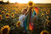 Beautiful young woman in white dress and scarf enjoying summer day in sunflowers field