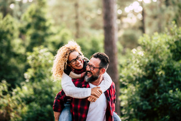 Happiness and cheerful people concpet with joyful couple playing and having fun together in the wood country side - adult man and woman in relationship carrying and laughing a lot together outdoor stock photo