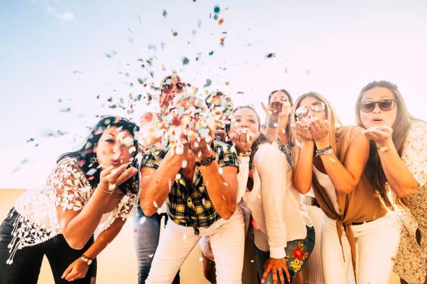 le bonheur et le concept joyeux - groupe de personnes heureuses de femmes célèbrent. tous ensemble soufflant des confettis et s'amusant - la veille du nouvel an et l'événement de fête pour le groupe de belles filles - fond clair blanc - festivité photos et images de collection