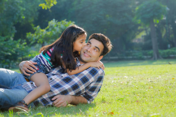 Happiness and love. stock photo Public Park, Season, Springtime, Summer, India little girl kissing dad on cheek stock pictures, royalty-free photos & images