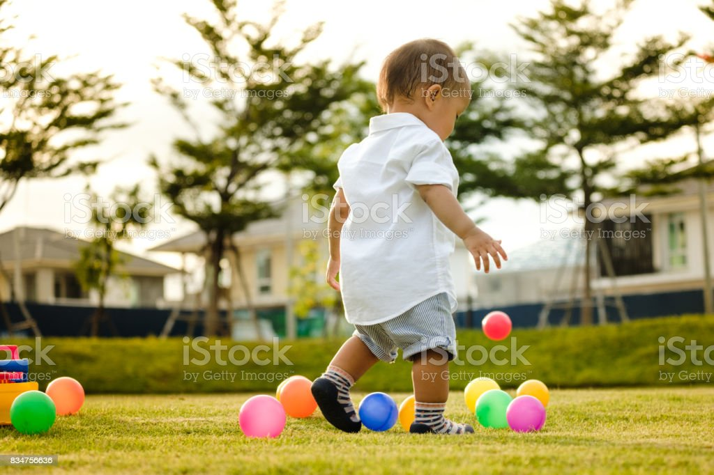 happiness Asian boy playing toy at outdoor park,Beautiful sunrise stock photo