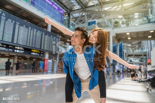 istock Happiness Asian couple traveler at the flight information screen in moddern an airport, lifestyle travel and transportation concept. 842907412