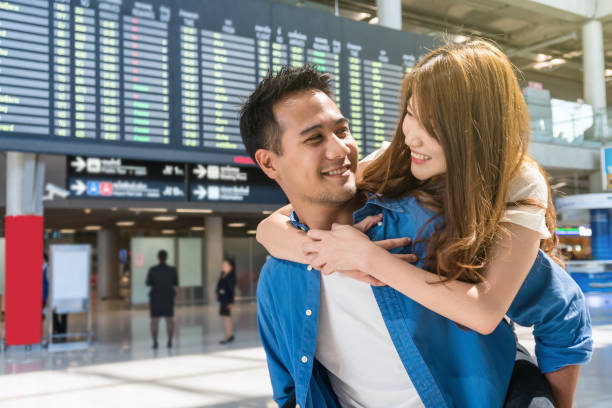 happiness asian couple traveler at the flight information screen in modern an airport, lifestyle travel and transportation concept. - aids healthcare foundation foto e immagini stock