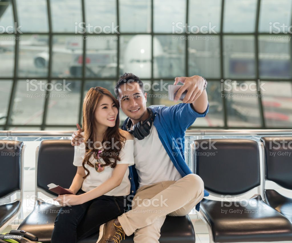 Happiness Asian couple traveler  taking a selfie with smart phone camera in smile action while waiting for airplane depart in modern an airport, travel and transportation with technology concept. stock photo