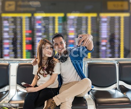 istock Happiness Asian couple traveler  taking a selfie with smart phone camera in smile action while waiting for airplane depart in modern an airport, travel and transportation with technology concept. 869328846