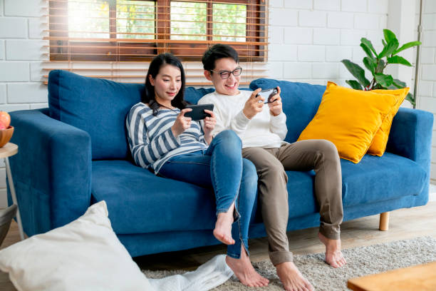 happiness asian sweet couple enjoy game on smartphone together living room home background - asian with phone house background stock photos and pictures