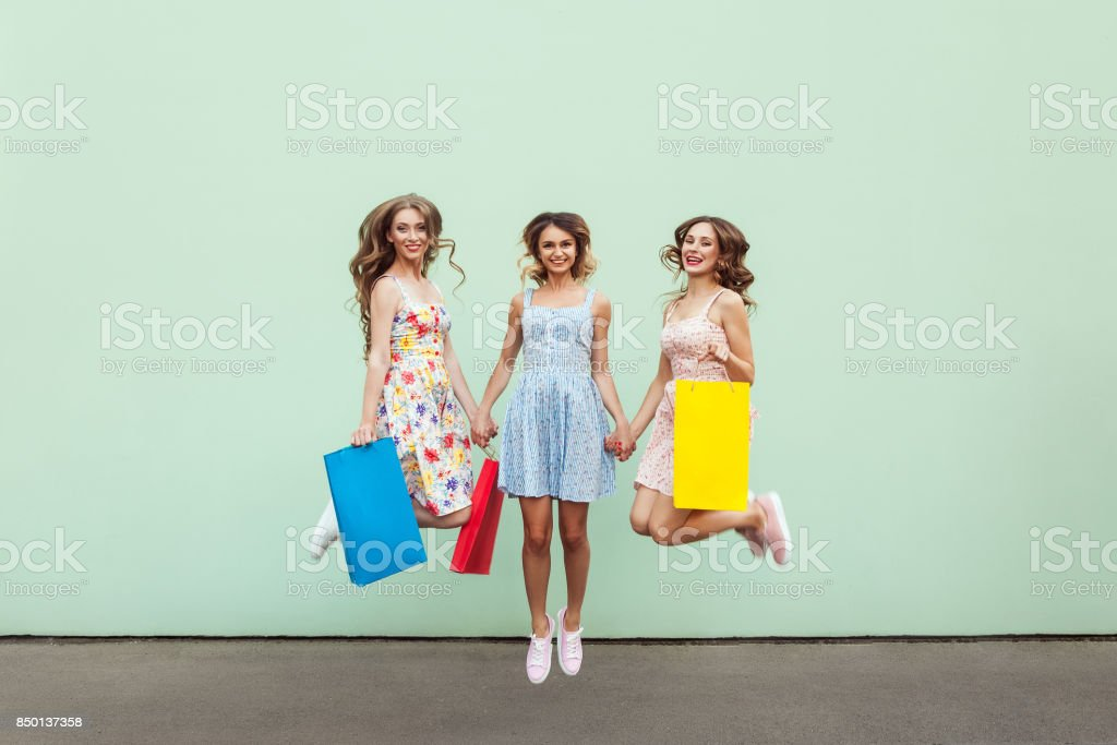 Happiness beautiful three friends jumping from happy with colorful packets after shopping. stock photo