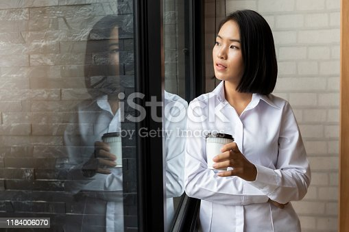 Happiness businesswoman holding takeaway coffee cup while standing at the window in the office.