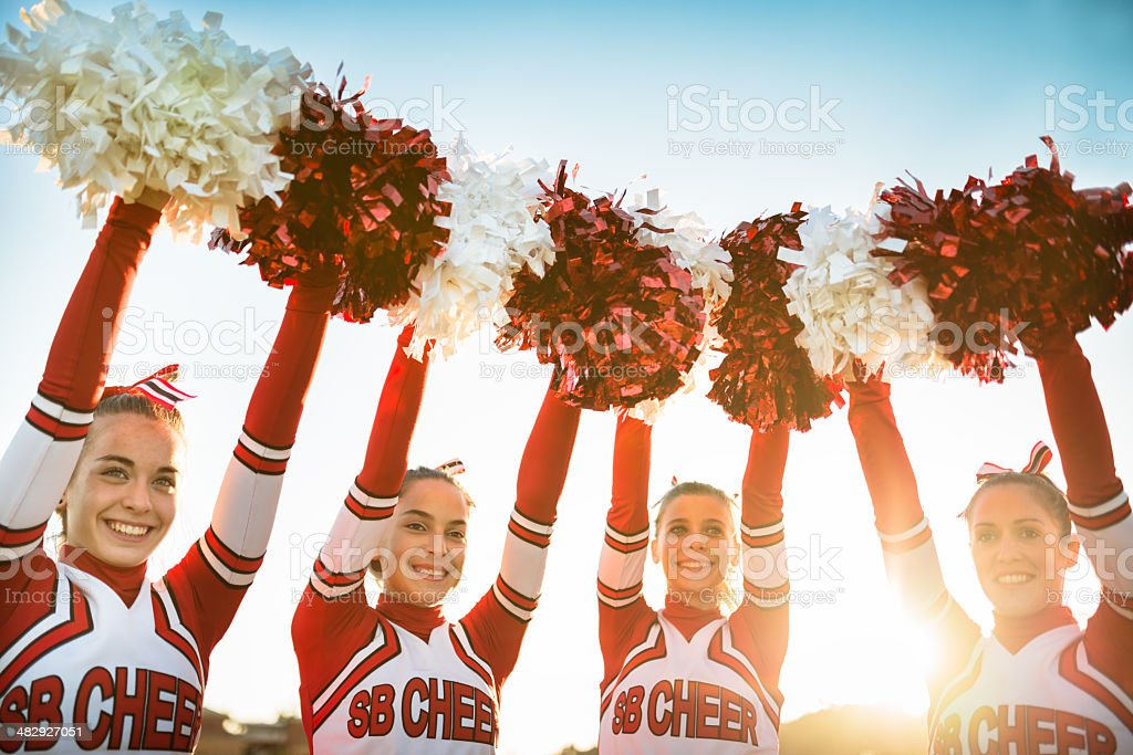 Happiness cheerleaders posing with pon-pon and arm raised stock photo