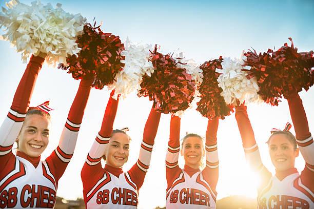 happiness cheerleaders posing with pon-pon and arm raised - pompon stockfoto's en -beelden