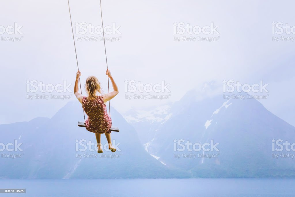 happiness concept, happy girl child on the swing on beautiful mountain landscape stock photo