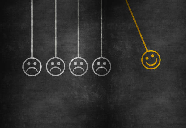 Happiness concept with happy and sad faces on newton's cradle on blackboard stock photo
