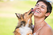 istock happiness concept with young beautiful laughing lady with short black hair and puppy dog shetland kissing her on the face with love and playful. friendship and together happy family alternative millennial 1127269726