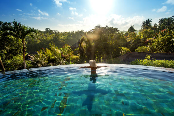 happiness concept. Woman sunbathing in infinity swimming pool at luxurious resort stock photo