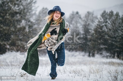 Happy woman jumping in the snow