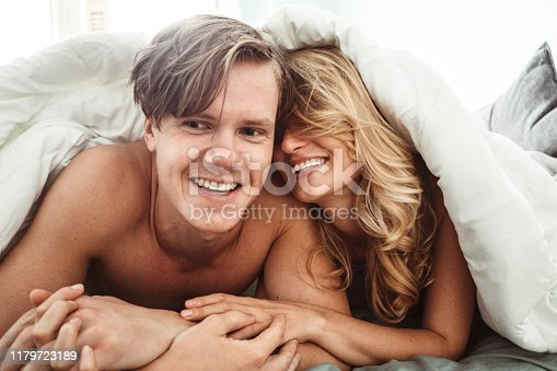 505826794 istock photo happiness couple lying down in the bed 1179723189