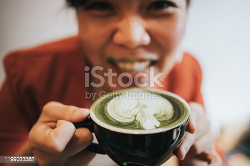 Close up of Thai designer women while drinking hot green tea matcha latte at the coffee shop with dirty lip