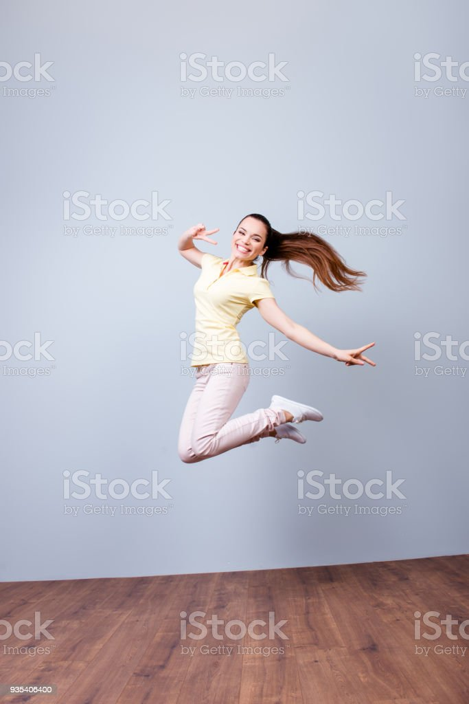 Happiness Dream Fun Joy Concept Very Excited Happy Girl Is Jumping Up  Wearing Casual Clothes Gesturing A Peace Sign Stock Photo & More Pictures  of