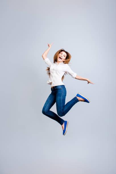 glück, traum, spaß, freude-konzept. sehr aufgeregt, glückliches mädchen springt oben auf einem grauen hintergrund, tragen legere kleidung, gestik ein friedenszeichen - damen jeans sale stock-fotos und bilder